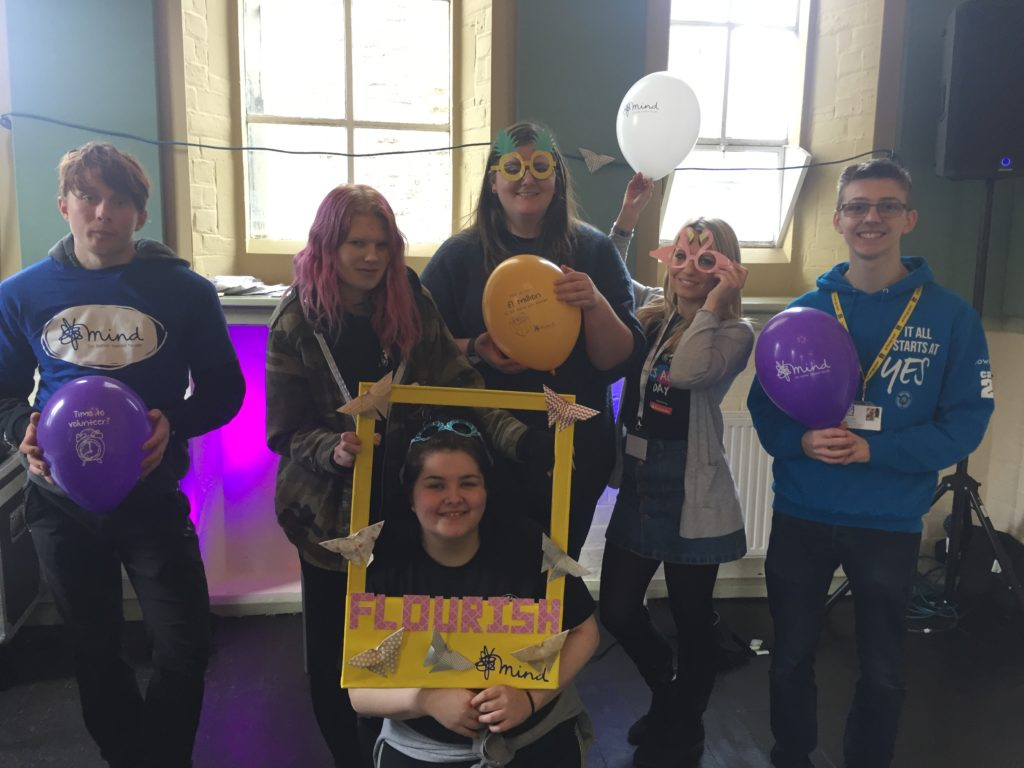 Photo of five people standing with balloons and a poster about mental health awareness