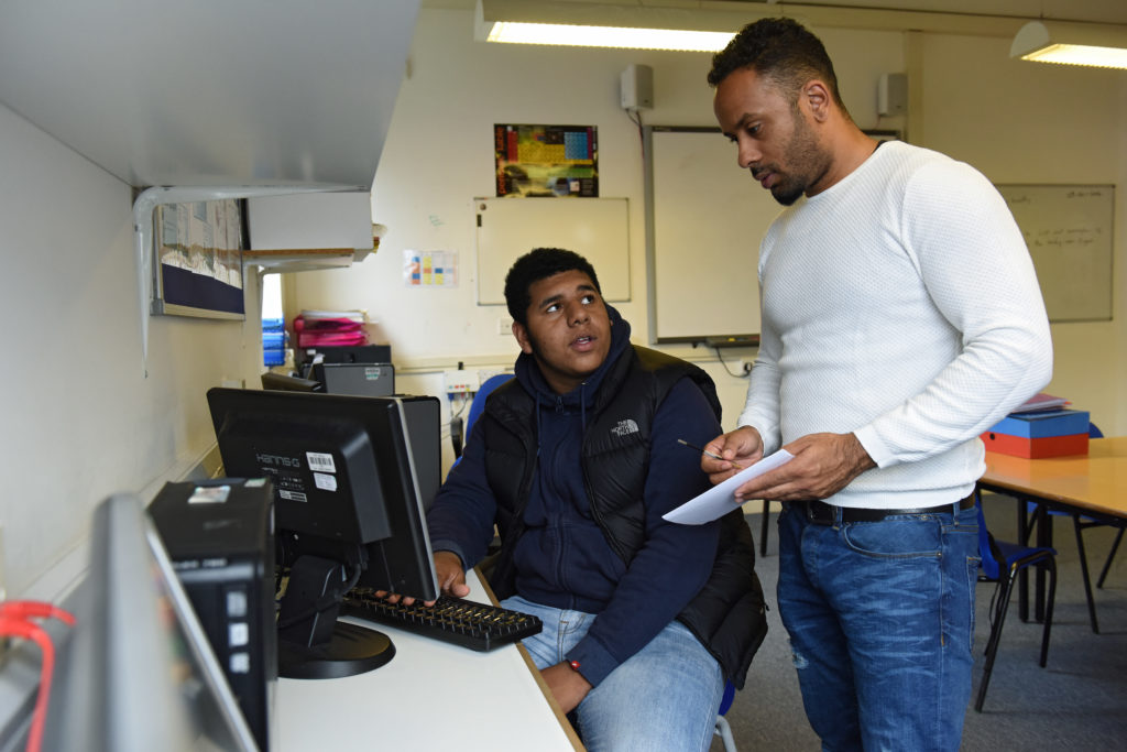 A picture of a young man sitting at a computer with an older man sitting above him giving instructions.