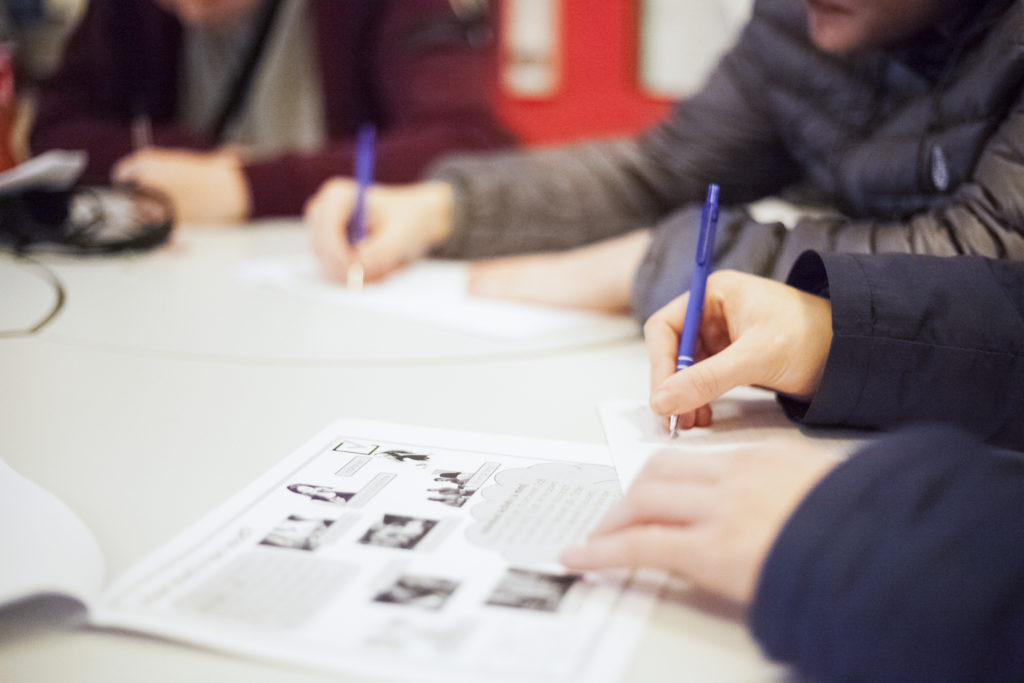 photo of student hands writing on paper